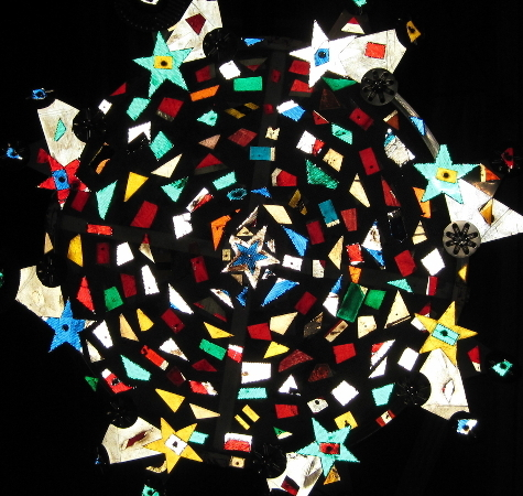 An abstract image of a wheel made out of shapes and stars; an abstract representation of At the Threshold